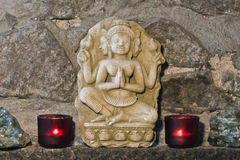 Representation of Buddha, stone carving, with  candles and flowers, Thailand Royalty Free Stock Image