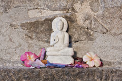 Representation of Buddha, stone carving, with flowers, India Stock Photography