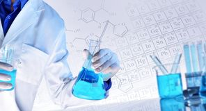 Representation of chemical sciences teaching concept. Worker equipped with workwear and laboratory chemical material with representation of chemical elements and stock photos