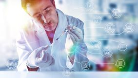 Representation with medical research icons with medical scientist. With syringe and vial in hands behind a white table. Horizontal composition stock photos