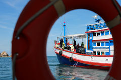Represente un mar de la pesca del barco del salvavidas del azul y del melocotón Fotografía de archivo
