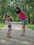 Reprimand in the park. Mother is disciplining her 6-8 years old daughter. Girl's looking frightened Royalty Free Stock Photography