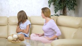 Reprimendas desapontados da mãe sua filha, que a ignora, sentando-se no sofá na sala de visitas filme