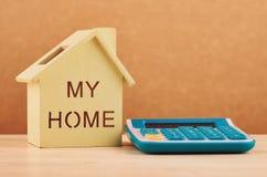 Reproducción y calculadora de la casa en el escritorio de madera para el préstamo hipotecario y el financiamiento fotos de archivo libres de regalías