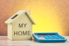 Reproducci?n y calculadora de la casa en el escritorio de madera para el pr?stamo hipotecario y el financiamiento fotos de archivo