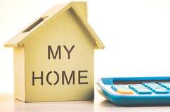Reproducci?n y calculadora de la casa en el escritorio de madera para el pr?stamo hipotecario y el financiamiento foto de archivo libre de regalías