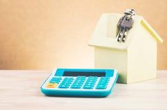 Reproducci?n y calculadora de la casa en el escritorio de madera para el pr?stamo hipotecario y el financiamiento imagenes de archivo