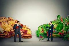 Représentant végétarien de nourriture combattant le type malsain de nourriture grasse d'ordure avec des gants de boxe Photographie stock