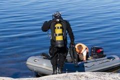 Repubblica di Carelia, Russia - 20 agosto 2015: Condizione del subaqueo vicino alla barca che controlla attrezzatura e che prepar fotografia stock