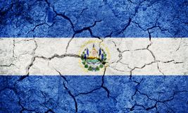 Republic of El Salvador flag. On dry earth ground texture background stock image