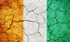 Republic of Ivory Coast flag. On dry earth ground texture background Royalty Free Stock Image