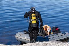 Republic of Karelia, Russia - August 20, 2015: Scuba diver standing near the boat checking equipment and preparing to dive stock photo