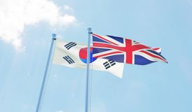 Republic of Korea and Great Britain, two flags waving against blue sky Royalty Free Stock Images