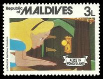 Alice in Wonderland and keyhole. Republic of Maldives - stamp 1980: Color edition on Walt Disney, shows Alice in Wonderland and keyhole royalty free stock photos