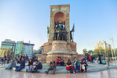 Republic Monument at Taksim Square in Istanbul. ISTANBUL, TURKEY - APRIL 28, 2017: People sitting around Republic Monument at Taksim Square in Istanbul. The Stock Photo