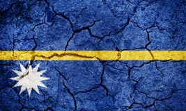 Republic of Nauru flag. On dry earth ground texture background stock photography