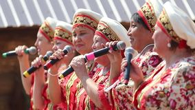 REPUBLIC OF TATARSTAN, RUSSIA: 04.07.2019 - Women in traditional tatar clothes stay in a row and singing with the. Microphone - Mid shot stock footage