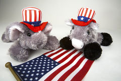 Republican and Democrat. Elephant representing the Republican Party and Donkey representing the Democratic Party in red, white and blue Stars and Stripes hats stock image
