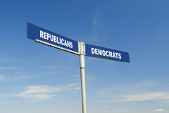Republicans vs Democrats signpost. Two-way metal signpost indicating Republicans and Democrats parties over blue sky Stock Image