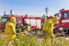 REPUBLIKA CZECH, DOBRANY, 4 CZERWIEC, 2014: Obsługuje w ochronnym hazmat kostiumu, samochodach strażackich i obraz royalty free