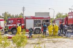 REPUBLIKA CZECH, DOBRANY, 4 CZERWIEC, 2014: Obsługuje w ochronnym hazmat kostiumu, samochodach strażackich i obrazy royalty free