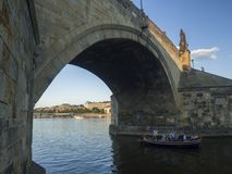 Republika Czech, Praga, Wrzesień 8, 2018: Łódź z turystą zaludnia żeglowanie pod Charles mosta łukiem na Vltava rzece, złota godz fotografia stock