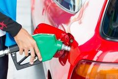 Repuesto del combustible adentro al coche rojo fotos de archivo libres de regalías