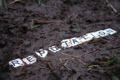 Reputation trampled in the mud. Letters spelling `reputation` being trampled in the mud Stock Photography
