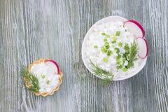 Requeijão natural fresco em uma bacia cerâmica branca na tabela de madeira azul Aneto verde Refeição saudável do eco orgânico, pr fotos de stock