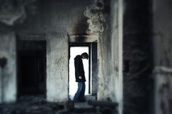 Requem for a hope. Single sad man standing in the door within the dark trashy interior. Shallow depth of field due to the tilt lens added Royalty Free Stock Photos