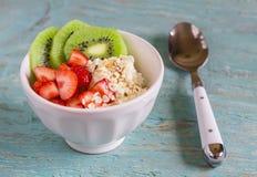 Requesón con las fresas, kiwi, miel, cereales y semillas del lino - una comida sana, desayuno sabroso y sano o bocado Fotografía de archivo libre de regalías