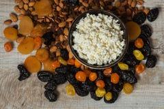 Requesón en el plato blanco Pasas, albaricoques secados, mandarines secados y almendras en un fondo de madera ligero Foto de archivo