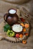 Requesón en un plato de la arcilla, leche, uva, albaricoques en fondo de madera Fotografía de archivo