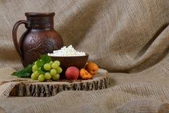 Requesón en un plato de la arcilla, leche, uva, albaricoques en fondo de madera Imagen de archivo