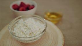 Requesón fresco para el requesón del desayuno en una placa Requesón con la miel y las bayas en la tabla almacen de metraje de vídeo