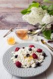 Requesón ruso con las bayas, menta de la miel, foco selectivo, desayuno sano Imagenes de archivo