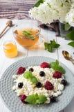 Requesón ruso con las bayas, menta de la miel, foco selectivo, desayuno sano Fotografía de archivo