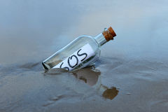 Request for help in a bottle on the beach. Bottle found on the deserted beach with a message inside Stock Image