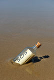 Request for help in a bottle on the beach. Bottle found on the deserted beach with a message inside Stock Photography