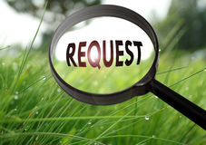 Request. Magnifying glass with the word request on grass background. Selective focus royalty free stock photos