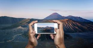 Resa Asien, handen som tar fotoet av monteringen Bromo som är vulkaniskt i Indonesien, vid den smarta telefonen för mobilen royaltyfri foto