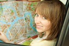 Den unga kvinnan med vägen kartlägger i bil under vägen snubblar Arkivfoton