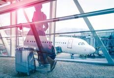 Resa begreppet med kvinnan på porten för flygplatsterminalen Royaltyfria Bilder