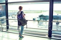 Resa det turist- anseendet med bagage som håller ögonen på på flygplatsfönstret royaltyfri fotografi