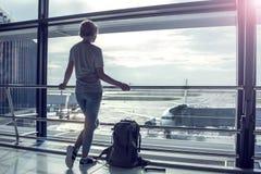Resa det turist- anseendet med bagage som håller ögonen på på flygplatsfönstret arkivbilder
