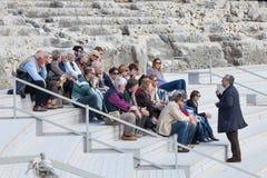 Resa handboken med gruppen av turister som sitter på forntida moment Royaltyfri Foto