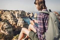 Resa kvinnan på en fotvandra slinga genom att använda smartphonen, lopp och aktivt livsstilbegrepp arkivfoto