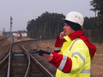 Resa med tåg arbetaren, teknikern i skyddande arbetskläder och hjälmen som talar vid telefonen järnvägspår på bakgrunden Royaltyfri Fotografi