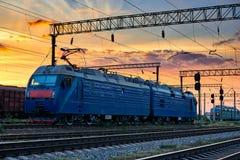 Resa med tåg infrastruktur under härlig solnedgång och färgrik himmel, drev och vagnar, trans. och det industriella begreppet Arkivfoton