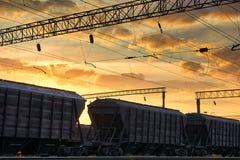 Resa med tåg infrastruktur under härlig solnedgång och färgrik himmel, railcaren för torr last, trans. och det industriella begre Fotografering för Bildbyråer